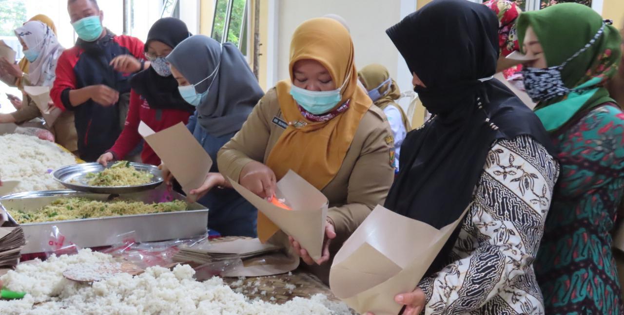 relawan sedang membungkus ribuan nasi
