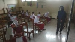 : Seorang guru sedang mengajar siswa